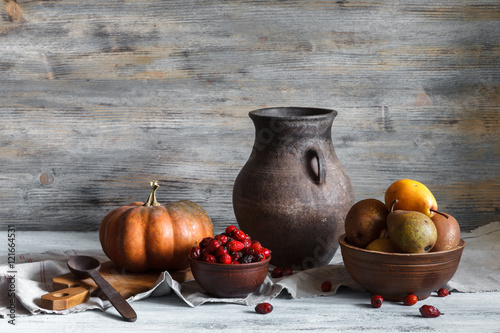 Fotografía  Still life in a rustic style: a set of pottery, pumpkin and pears