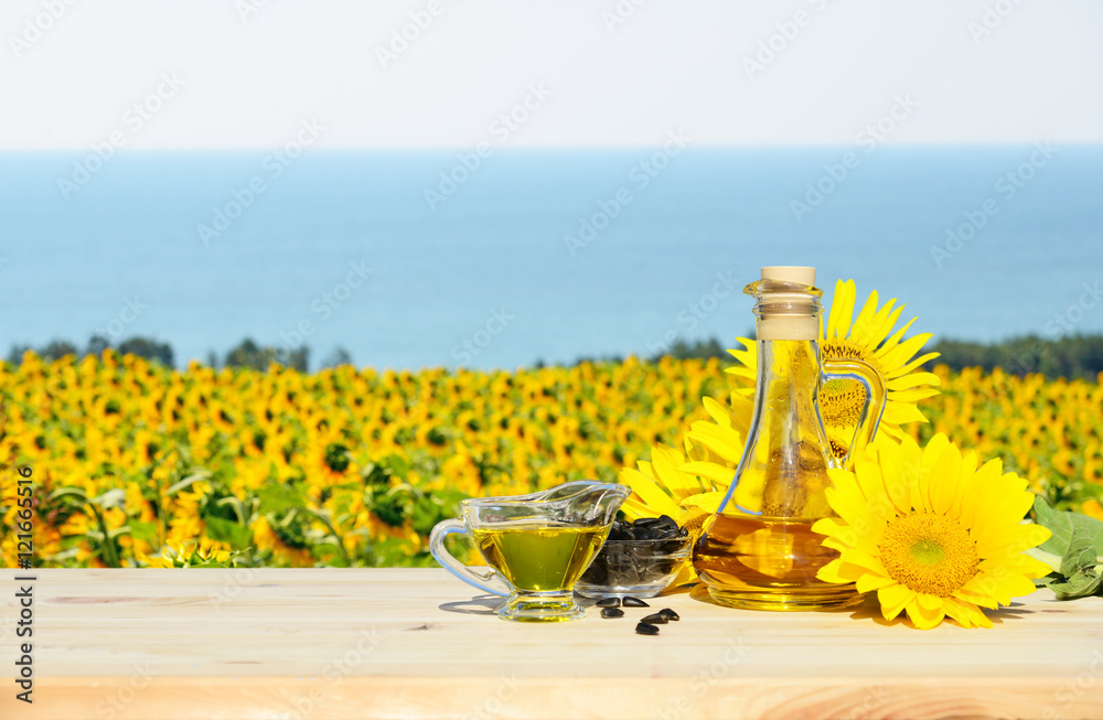 Sunflowers, seeds and sunflower oil. In the background a field of sunflowers and sea