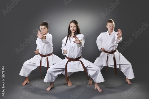Obrazy Karate   one-female-and-two-male-brown-belt-karate-doing-kata-on-the-gray-background