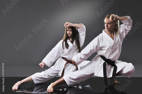 Garden Poster Martial arts Two beautiful young female karate doing kata on the gray backgro