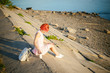 girl in pale pink dress with red hair and backpack walking along river bank, sitting on the sandy shore