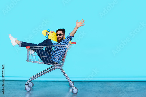 Photo  Side view of cheerful young man sitting in shopping cart