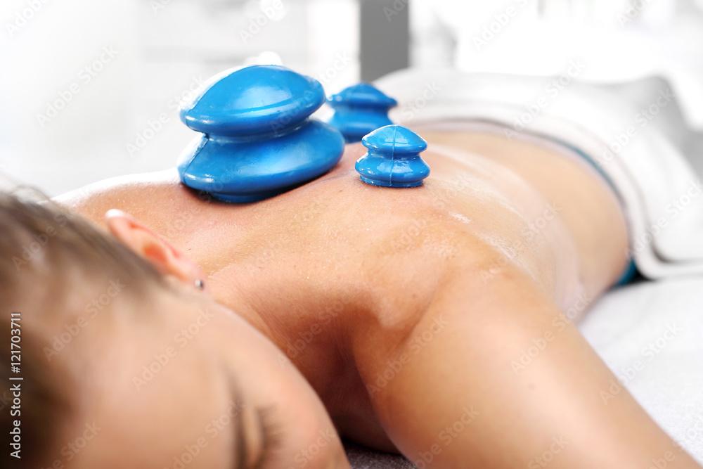 Fototapeta Medycyna alternatywna. Masaż. Masażysta masuje plecy kobiety gumową bańką chińską.