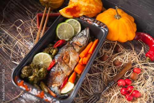 Photo Stands Grill / Barbecue fish on the baking dish with cherry tomatoes, orange, garlic, on