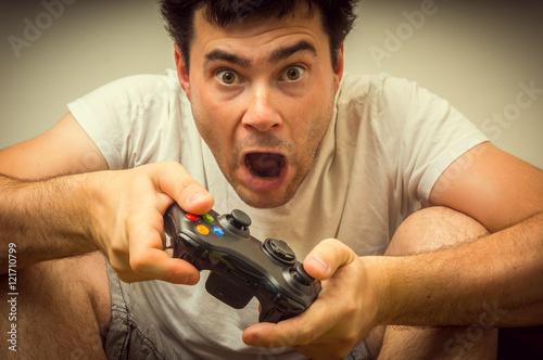 Zdjęcie XXL Emocjonalny młody człowiek uzależniony od grania w gry wideo