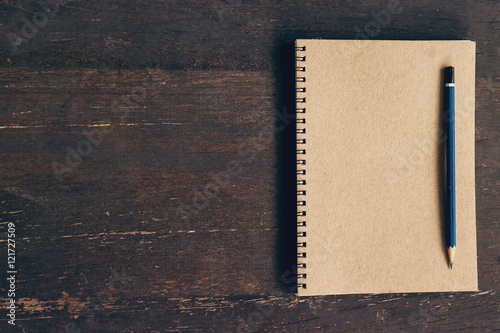 Fototapeta  Top view notebook and pen on wood table with space, Vintage filt