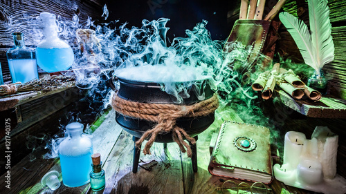 Photo  Mysterious witcher cauldron with books and potions for Halloween