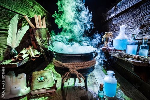 Photo  Mysterious witcher cauldron with blue potions and books