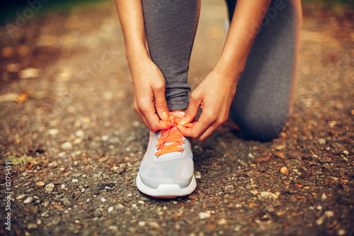 Fotomural  Close-up of female runner lacing her shoes