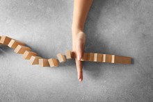 Female Hand Stopping Domino Effect On Grey Background