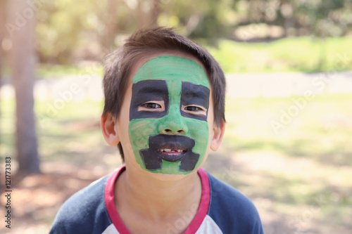 Young boy with fun green and black face painting Canvas Print