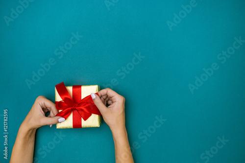 Photo  Female hands holding gift on blue background