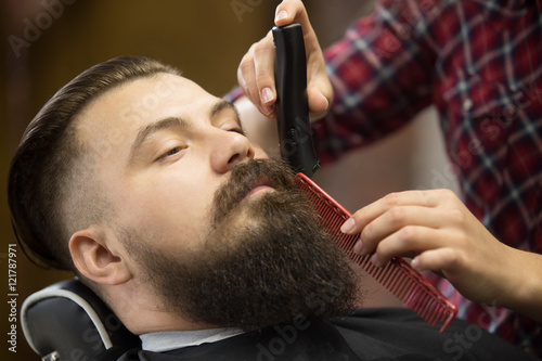 Close-up portrait of handsome young bearded caucasian man getting trendy beard haircut in modern barber shop. Hairstylist girl working, serving client, doing beard grooming using shaver and comb
