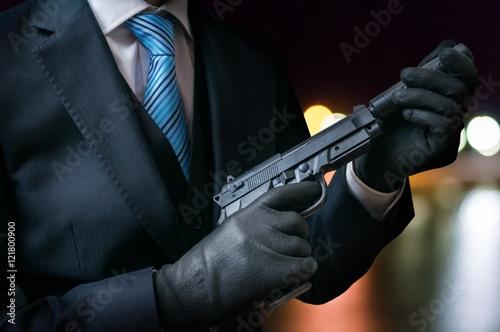 Fotografie, Obraz  Killer holds gun with silencer in hands at night.