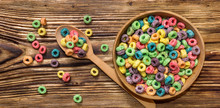 Wooden Spoon And Wooden Bowl With Colorful Cereal