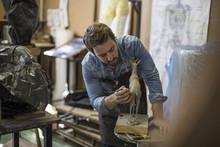 Sculptor Working In Studio On Animal Figurine