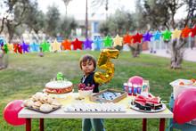 Little Boy Hiding Behind Golden Balloon At Laid Birthday Table