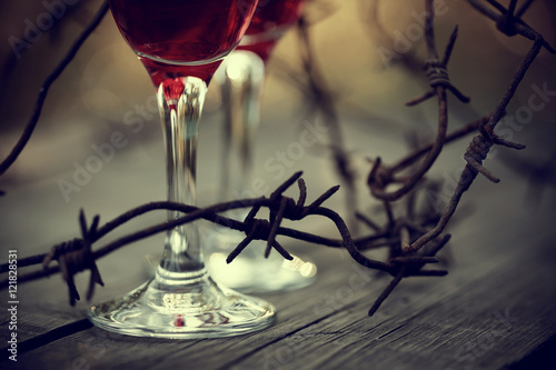 Fotografía Rusty barbed wire and glasses with red wine.