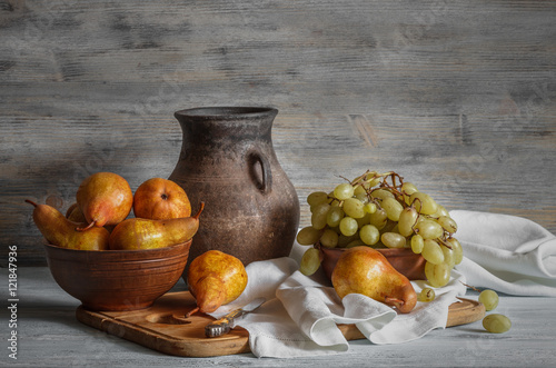 Still life in a rustic style: a set of clay dishes, grapes and pears on a wooden table. Natural light from the windows.