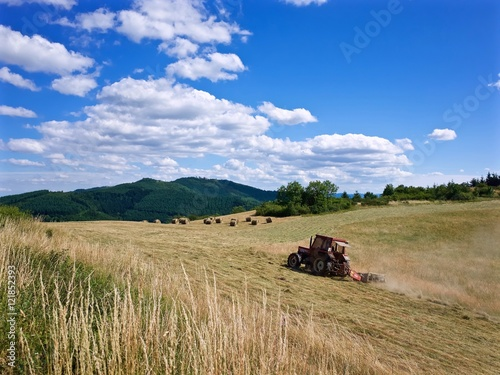 Fotobehang Cultuur Tractor Baling Hay In Field