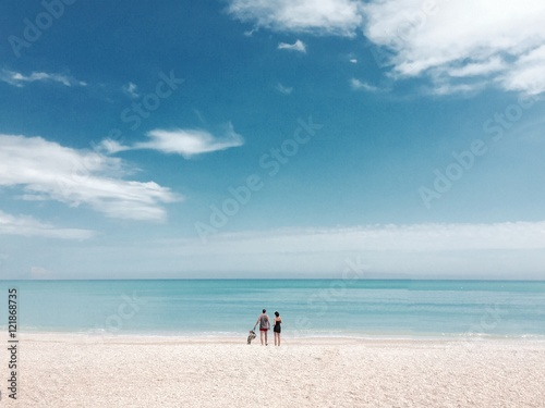 Deurstickers Strand Two People Standing On Idyllic Sandy Beach, Horizon Over Sea, Pastel Colored
