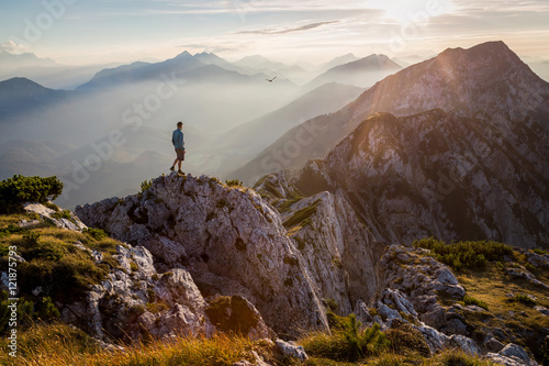 Foto op Aluminium Bergen Man standing on a mountain summit at sunset