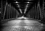 Środek drogi patrząc w dół mostu z nadjeżdżającym samochodem - 121890104