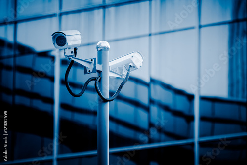surveillance camera front of modern building,blue toned.