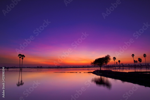Fotobehang Snoeien Silhouette twilight sunset sky reflect on the water with palm tree landscape