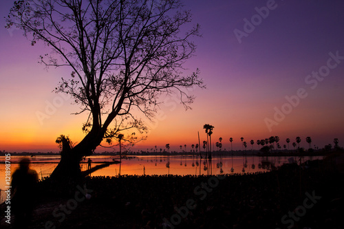 Fotobehang Aubergine Silhouette twilight sunset sky reflect on the water with palm tree landscape