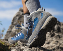 Close Up Of Hiking Boots And Legs Climbing Up Rocky Trail And Reaching The Top Of A Mountain