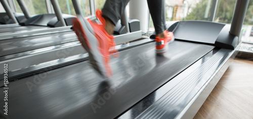 Obraz na plátně Female foot running on treadmill - motion blur