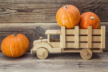 Wooden Toy Truck With Pumpkins In The Back On A Background Of Wo