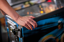 Young Woman Playing On The Pinball Machine