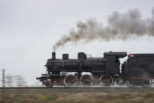Old steam locomotive running on rails плакат