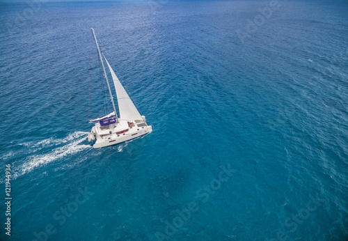 Slika na platnu Aerial view of catamaran sailling in ocean