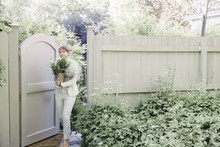 Woman Entering A Garden Through A Gate, Carrying A Bunch Of White Flowers.