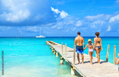 Foto op Plexiglas Caraïben Back view of a happy family on tropical beach. Family standing on a wooden pier.