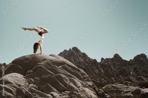 Frau macht einen Handstand auf einem Fels