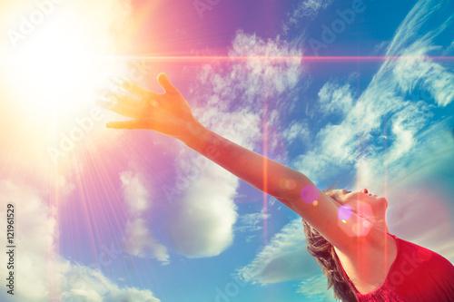 Mujer con los brazos abiertos al cielo azul tomando aire fresco.Concepto de bienestar.Desarrollo personal y felicidad.