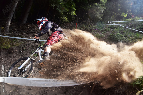 Sport race Mountain biker extreme and fun downhill track. Dirt splash.