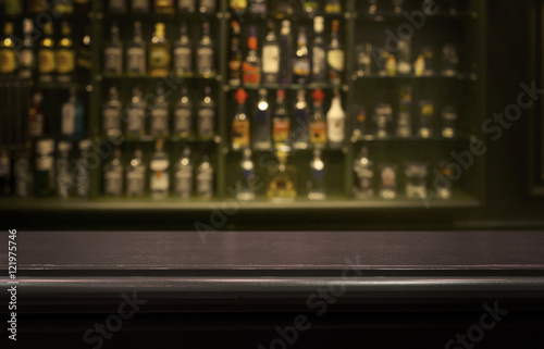 Fotografía  Empty wood counter  bar  table with  blur  bottle background.
