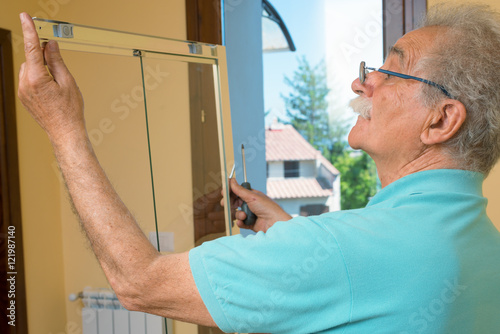 Senior man installing and checking a shower box do it yourself senior man installing and checking a shower box do it yourself concept solutioingenieria Image collections
