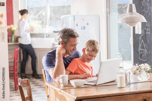 Fototapeta  Cheerful father and son using a laptop while having breakfast obraz na płótnie
