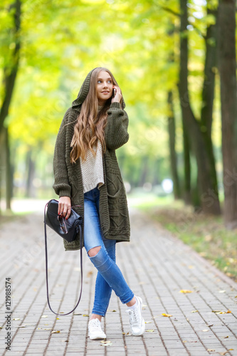 Fotografía  Beautiful young woman in green knitted cardigan with a hood walking in autumn park and talking mobile phone