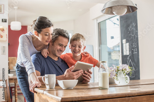 Obraz A family using a tablet while having breakfast in the kitchen - fototapety do salonu