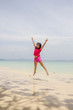 happy young girl jumping on the beach