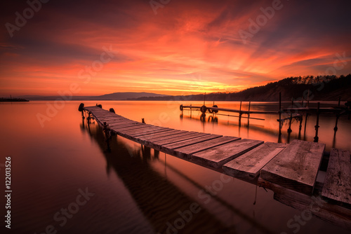 Spoed Foto op Canvas Koraal Fire in the sky / Magnificent long exposure sea sunset with fisherman piers at the Black sea coast, Bulgaria