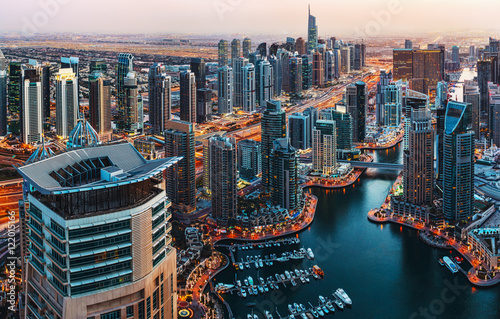 Fantastic view over illuminated architecture of a big city at night. Dubai Marina, United Arab Emirates. Scenic travel background.