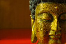 Gold Buddha Tranquil Face On Dark Red Background, Copy Space